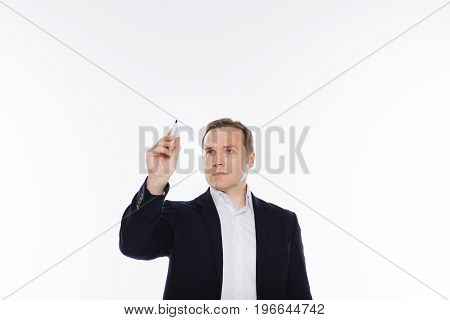 Writing on the wall. Handsome elegant focused gentleman standing isolated on white background and using a marker while making some notes