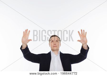 Imagine the world. Determined active enthusiastic man looking on something invisible while acting on set and posing isolated on white background