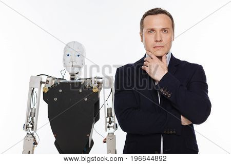 Ambitious creator. Classy passionate professional inventor holding his chin while posing with a robot and standing isolated on white background