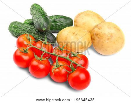 A close-up of fresh autumn vegetables isolated on a white background.  Tasteful green cucumbers, a juicy red bunch of tomatoes and nutritious uncooked potatoes. Ingredients for traditional dishes.