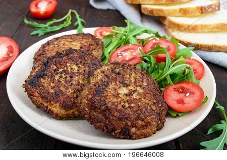 Juicy cutlets on a plate with a salad of tomatoes and arugula on a dark wooden background.