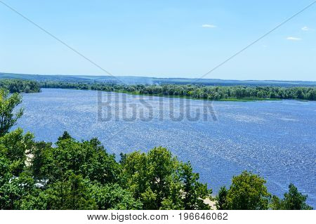 Beautiful landscape on a wide river with a green banks bird's-eye view. Sunny summer day.