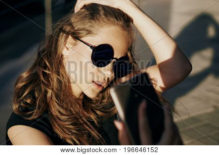 Young beautiful woman in sunglasses walking along the street in the city.