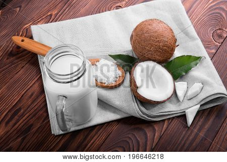 A beautiful composition of coconuts on a gray burlap sack and a mason jar full of delicious coconut milk. A top view of a whole and a cracked coconut with green leaves and a spoon with coco flakes.