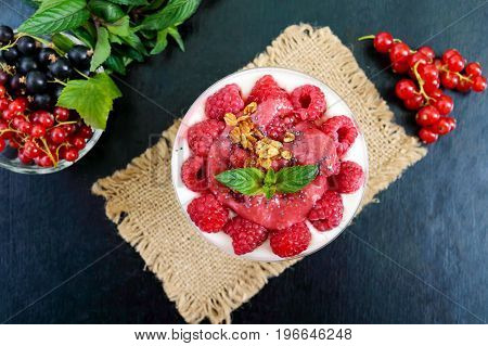 Delicious healthy dessert: yoghurt fresh berries granola raspberry sauce on a black background. The top view