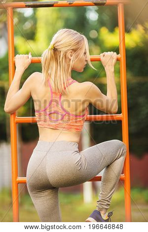 Sexy young fitness girl pulls up on street sport gym. Blonde fitness woman in sport wear with perfect fitness body on street workout performing abdominal exercises on the horizontal bar