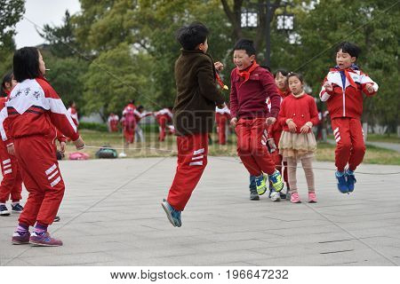 SUZHOU CHINA - MARCH 22: Chinese school children play in park on March 22 2016 in Suzhou China. Suzhou is a major economic center and focal point of trade and commerce in Jiangsu Province China.