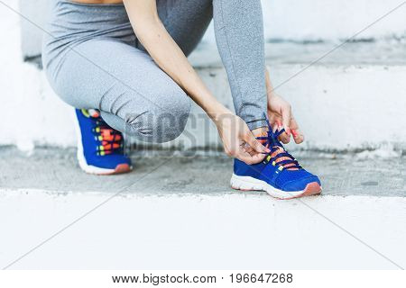 Attractive sportswoman tying shoelace and getting ready for fitness. Young woman runner tying shoelaces with copy space healthy lifestyle and sport concepts.