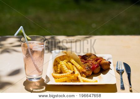 Currywurst and pommes on recyclable dishes, paper plate