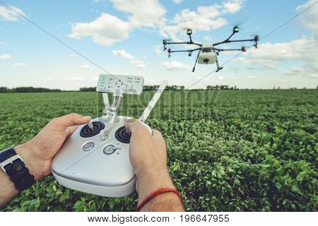 The man control octocopter or remote control for the drone in the hands for take a picture on sky. Agriculture drone flies over the green field.