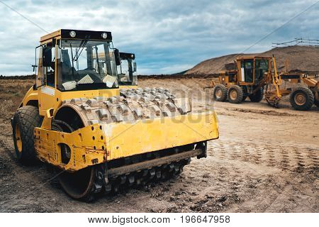 Heavy Duty Machinery Working On Highway Construction Site. Bulldozer, Dumper Truck, Soil Compactor A