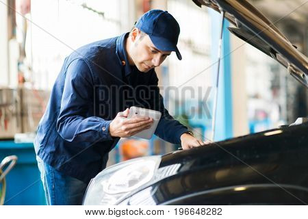 Mechanic using a tablet in his garage