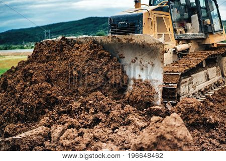 Yellow Mini Bulldozer Working With Earth And Soil While Doing Landscaping Works On Construction Site