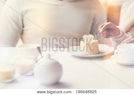 Time for a dessert. Close up of a delicious cake standing on the table in front of a nice happy young couple while being eaten