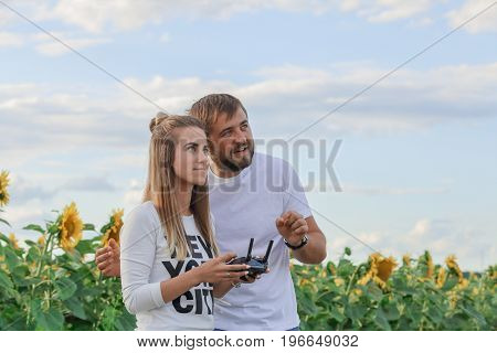 Young man teaches drone operation a beautiful woman. Happy young couple standing together outdoors.
