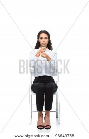 Attractive Serious Woman Gesturing Signed Language While Sitting On Chair, Isolated On White