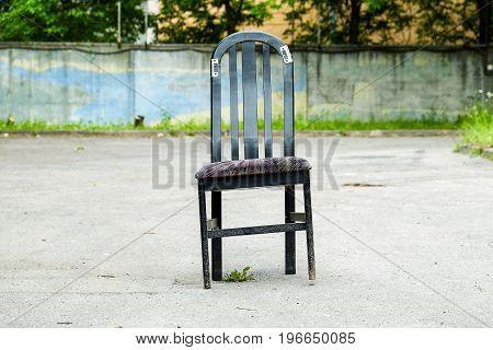 a lone broken chair on the asphalt road