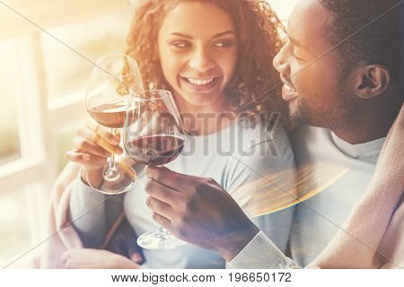 So wonderful. Pretty joyful beautiful woman holding a glass of wine and looking at her boyfriend while enjoying her time with him