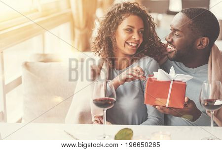 It is for you. Joyful nice afro american man holding a present and giving it to his girlfriend while having a date with her