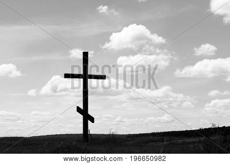 Black-and-white photo with wooden cross on sky background