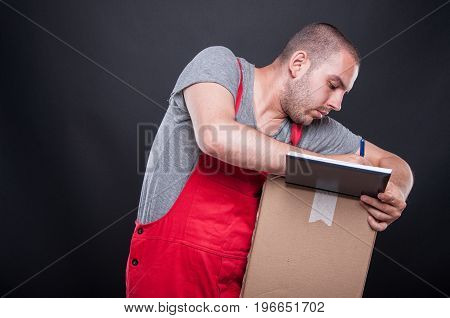 Mover guy writing on agenda on cardboard boxes on black background with copy text space