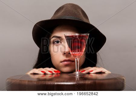 girl looks at camera through wineglass on gray background