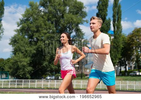 Couple Running On Arena Track.