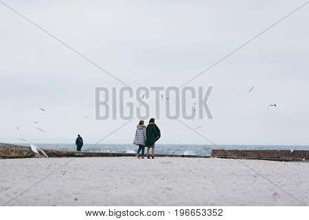 Girl Wearing Warm Casual Blue Coat Walking On The Beach Alone,sea Background,cold Toned Colors.lifes