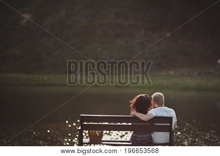 Couple Sitting On A Bench Looking At The Sea