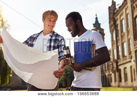 Do you see mistakes. Dynamic productive passionate guy meeting his friend at the campus and showing the blueprint of the building to him while expecting his help