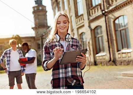 Updating the newsfeed. Young pretty clever girl texting her friend while walking around the campus and heading for the next lecture