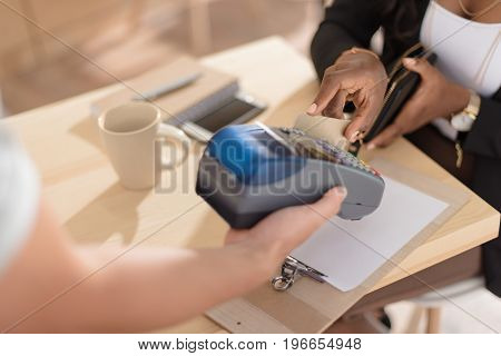 Cropped View Of  African American Woman Paying With Credit Card Through Terminal In Cafe
