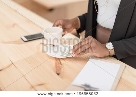 cropped view of african american woman with coffee cup paying with cash in cafe