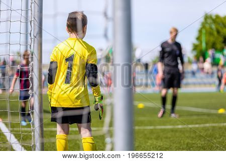 Soccer goalkeeper of youth team. Football tournament for kids. Children kicking soccer game. Soccer pitch in the background