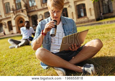 Just one more cup. Young bright curious guy sitting on the grass and studying for the test while sipping coffee from his cup