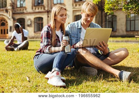 Team of learners. Young gorgeous motivated woman meeting her friend and helping him with the assignment while they both sitting in front of the university building