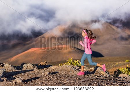 Trail running runner woman on mountain nature adventure training on rocky volcanic rocks path in mountains in high altitude with clouds over peaks.