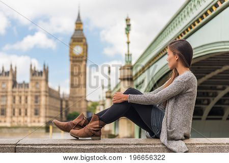 London young woman relaxing pensive thinking alone at Big Ben tower in urban Europe city. Asian girl lonely sad or depressed sitting outdoors in the city, England, UK, Great Britain.