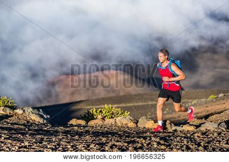 Trail running runner man on endurance run with backpack on volcano mountain. Ultra marathon race athlete on volcanic rocks path in mountains landscape.