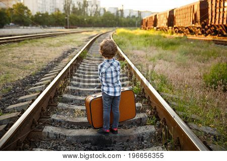 Back view of young boy wearing checkered shirt carrying brown suitcase standing on railways.