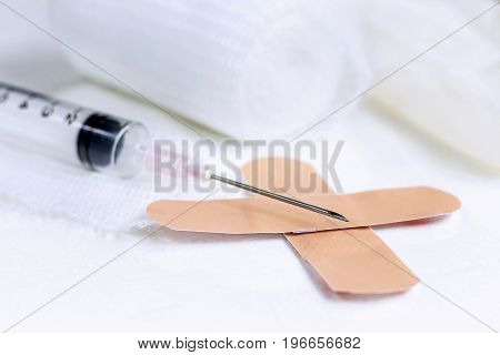 Syringe medical gauze bandage on white table.