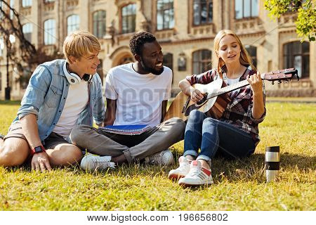 Real talent. Classy talented pretty girl sharing her new song with friends while they meeting at the campus and resting on the grass