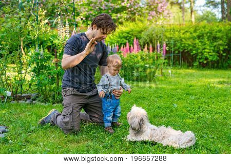Father teaching son how to command the dog in summer green garden