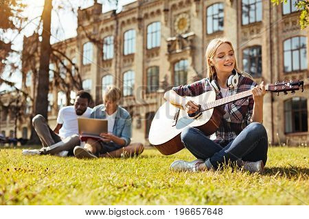 Practice makes perfect. Bright inspired creative girl playing guitar and singing while sitting on the grass in front of the university building