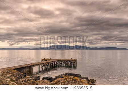 The ancient castle jetty at Portencross in Seamill Ayrshire Scotland with Arran hills in the back ground. The skys are heavy just before it rained as it always does in Scotland! The Cloud and Arran hills are reflected on the water.