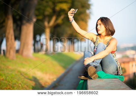 Teen ager girl gets selfie with smartphone.