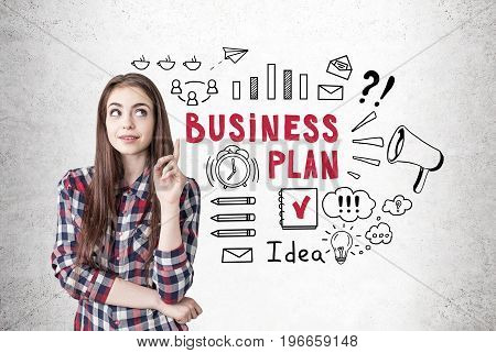 Portrait of a creative young woman wearing a checkered shirt and looking sideways while thinking and pointing upwards. Concrete wall background with a black and red business plan sketch