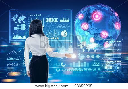 Glowing Earth hologram against a dark blue background with red placeholders and graphs. Black haired businesswoman. Toned image double exposure
