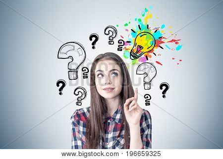 Portrait of a creative young woman wearing a checkered shirt and looking sideways while thinking and pointing upwards. Gray wall background with a bright light bulb and question marks around it.