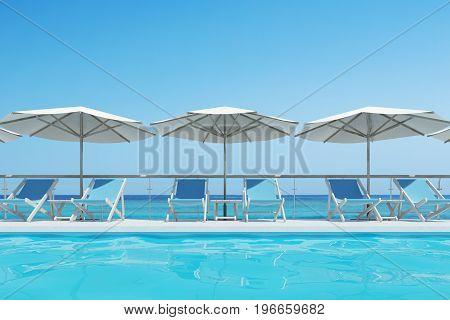 Blue deck chairs are standing under beach umbrellas near a swimming pool. A blue cloudless sky is above them. Close up. 3d rendering mock up
